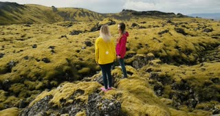 Aerial view of two woman standing on the rock, looking on the lava field in Iceland and dancing, feeling freedom, happy.