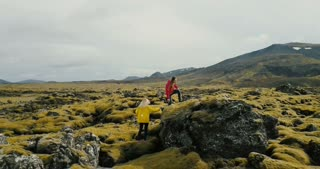 Aerial view of two woman walking on the lava field in Iceland. Tourists hiking on the rocks, feeling freedom and happy.