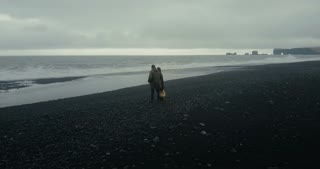 Aerial view of young couple standing on black volcanic beach near the troll toes rocks and enjoying on wave in Iceland.