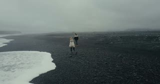Aerial view of young couple walking on the black volcanic beach in Iceland. Man and woman in lopapeysa throw rock on sea