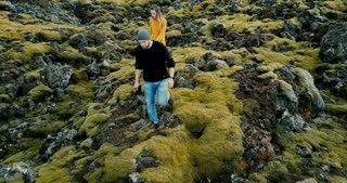 Aerial view of young stylish couple walking through the volcanic lava field in Iceland. Man and woman go to their car.