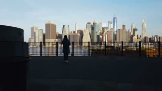 Aerial view of young woman standing on the pier in Brooklyn park, drone flying to Manhattan in New York, America.