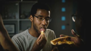 African American casual young man in glasses eating pizza at party. Happy friends enjoy fast food in the kitchen at home