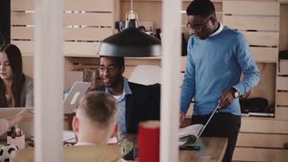 African American CEO businessman sitting by the table at office meeting with multiethnic business partners slow motion.