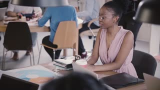 African American female businesswoman with smartphone sitting by the office table in busy modern coworking slow motion.