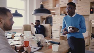 African American worker talking to company boss. Happy mixed ethnicity colleagues work in trendy loft office space 4K.