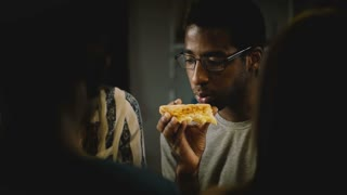 African American young man eating pizza at a casual house party. Young people enjoy fast food in the kitchen at home.
