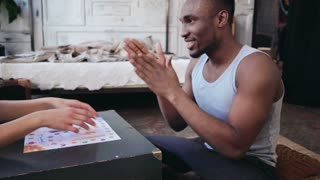 African handsome man in pajamas throws the dice and laughs. Multiethnic couple playing the board game on the floor.