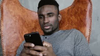 African male sitting in chair and thinking, holding Smartphone. Man remembers something good and starts typing messages.