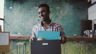 African man recently hired at company come into new office. Male hold box with personal belongings, greets with people.