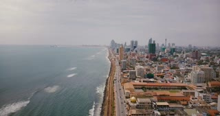 Amazing aerial view of Colombo, Sri Lanka. Drone flying over busy city street, ocean waves and modern Asian architecture