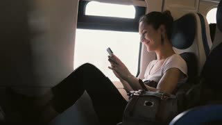 Amazing cinematic shot of beautiful European girl smiling, using smartphone app and looking out of moving train window.