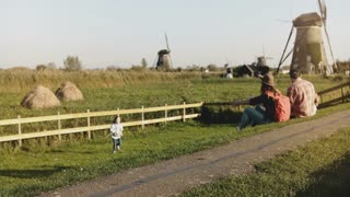 Amazing family sit together in a windmill farm. Dad, mom and kids enjoy wonderful bonding time together outdoors. 4K.
