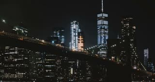 Amazing night Brooklyn Bridge timelapse, New York. Low angle. Highrise illumination lights and traffic passing by. USA