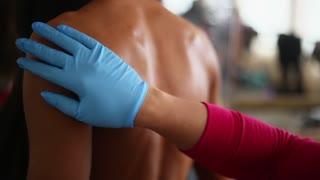 Applying body oil on female bodybuilder back. Getting ready for bodybuilding championship.