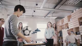 Asian man plays with football in office during break. Happy friends stand in circle, hold physical activity slow motion.