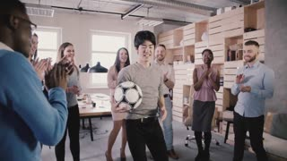 Asian man tries to hold football on head in office. Happy mixed ethnicity workers playing fun sports game slow motion.