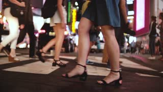 Atmospheric slow motion shot of young female legs walking across busy crowded street at night in Times Square, New York.
