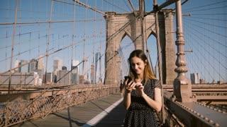 Attractive adult European woman talks to friends using smartphone video call app at Brooklyn Bridge, New York city 4K.