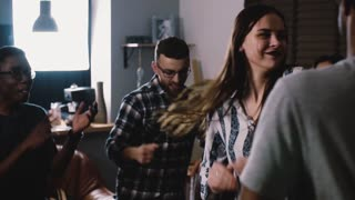 Attractive girl dancing together with her friends. Slow motion close up. Multi ethnic birthday house party celebration.