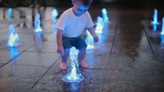 Attractive little boy running trough fountain and touching water jets. Child having fun on hot summer day.