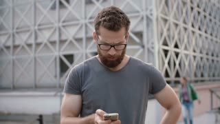 Attractive man with beard and glasses uses smartphone on the street. Guy surf the Internet, uses touchscreen technology.