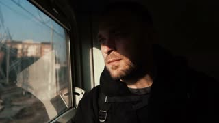 Attractive man with beard traveling by train. Handsome young male looking at window and thinking, sitting in the shadow.