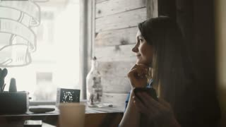 Attractive woman sitting near the window in cafe and holding the smartphone, using the wireless technology.