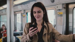 Attractive woman using smartphone in metro car. Beautiful young European girl in social network web app online. 5G. 4K