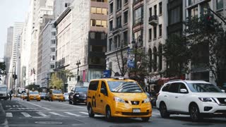 AUGUST 18, 2017 NEW YORK - Cars and yellow cab taxis passing by along big city street, then pedestrians start to cross.