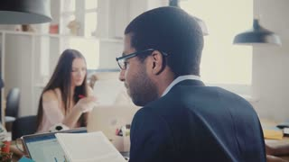 Back view African American businessman reading through documents at multiethnic office meeting, diagrams on laptop 4K.