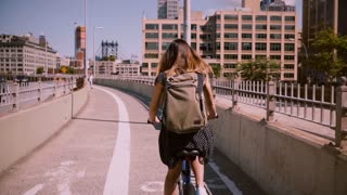 Back view female commuter riding a bicycle with backpack and golden hair blowing in the wind on a sunny day slow motion.