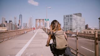 Back view female freelance worker with long flying hair enjoying weekend bike ride on Brooklyn Bridge, slow motion.