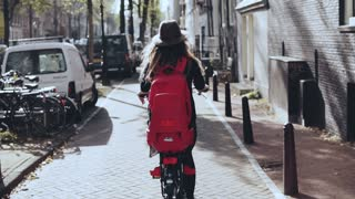 Back view. Female on a sunny city bicycle ride. Slow motion. Girl in stylish hat with red backpack on bike. Exploring.