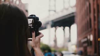 Back view female travel blogger with camera takes pictures of Brooklyn Bridge at Dumbo, New York City, walks away 4K.