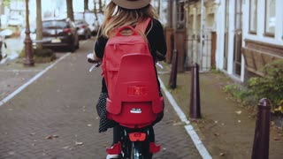 Back view. Female with red backpack on bicycle. Slow motion. Excited Caucasian tourist woman. Lifestyle beauty blogger.