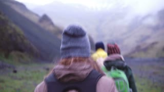 Back view. Group of young people hiking on the mountain early in the morning. Travelers going up together.