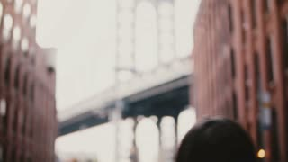 Back view happy female tourist with camera takes photos of Brooklyn Bridge from Dumbo viewpoint, New York, walks away 4K