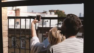 Back view happy romantic couple sitting at a small New York apartment balcony, taking smartphone selfie and having fun.