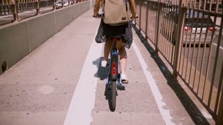 Back view happy woman with backpack riding a bicycle along a separate bike lane level on Brooklyn Bridge, New York City.