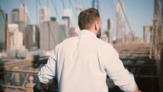 Back view of adult Caucasian man standing by Brooklyn Bridge rails, enjoying amazing cityscape view and walking away 4K.