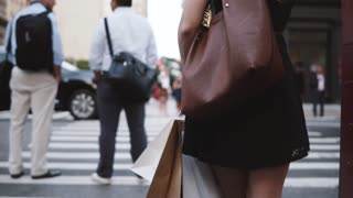 Back view of anonymous young woman with a stylish bag waiting to cross the street holding shopping bags slow motion.