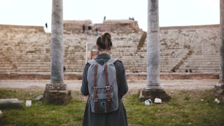 Back view of beautiful tourist girl with backpack standing in front of ancient amphitheater pillars in Ostia, Italy.