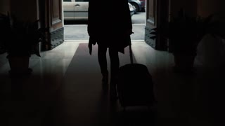 Back view of businesswoman walking with a suitcase in the tunnel. Girl goes out of entrance in the city. Slow motion.