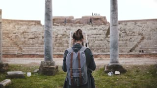 Back view of Caucasian tourist girl with backpack taking smartphone photo of ancient amphitheater pillars in Ostia Italy