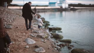 Back view of father and son walking along the shore, daughter runs to them. Brother and sister spending time with dad