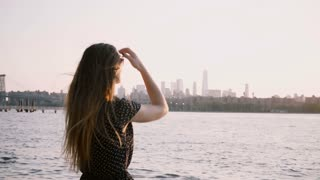 Back view of girl in sunglasses standing alone on sunset beach, hair blowing in the wind and arms raised in the air 4K.