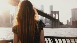 Back view of girl with hair blowing in the wind standing at river embankment, arms open near Brooklyn Bridge New York.