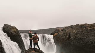 Back view of happy couple after hiking. Traveling man and woman stand near the waterfall in Iceland and raising hands up