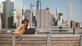 Back view of happy female traveler with hair blowing in the wind enjoying New York skyline, raising arms wide open.